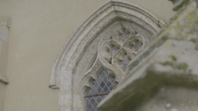 pan right shot of a gothic style window of the church of st mary in troston - ornate stock videos & royalty-free footage