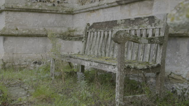 pan right shot of an old bench in the graveyard of the church of st mary in troston - moss stock videos & royalty-free footage