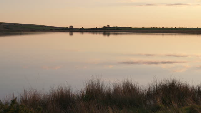 pan right shot of dozmary pool in cornwall at sunset - literature stock videos & royalty-free footage