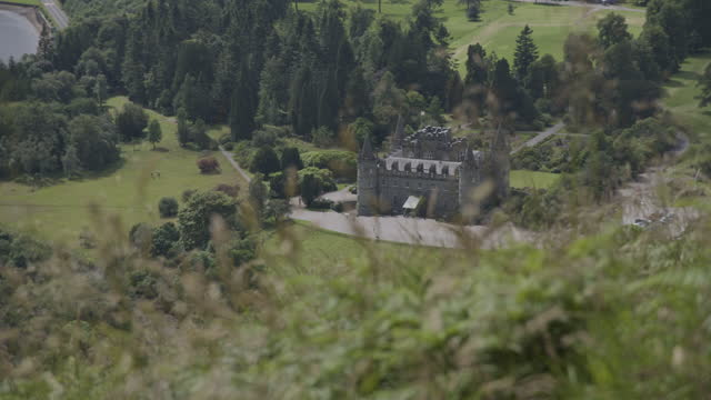pan right shot of inveraray castle seen through tall grass from dun na cuiache - rack focus stock videos & royalty-free footage