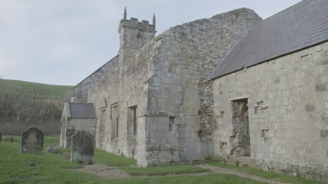 pan right shot of the graveyard and the ruins of st martins church in wharram percy in the deserted medieval village - tomb stock videos & royalty-free footage