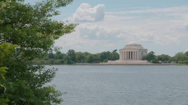 pan right shot of the thomas jefferson memorial with the tidal basin in the foreground - jefferson memorial stock videos and b-roll footage