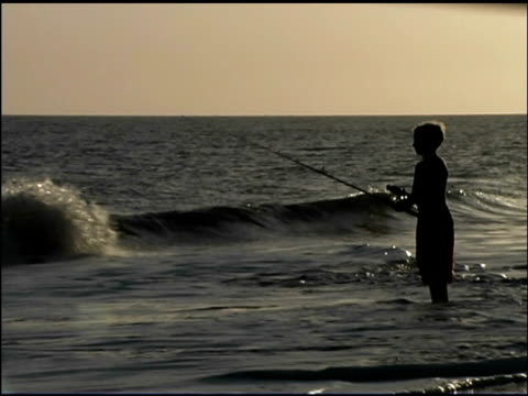 pan right silhouette of a boy fishing in the ocean surf. he is reeling in his line. - see other clips from this shoot 1135 stock videos & royalty-free footage