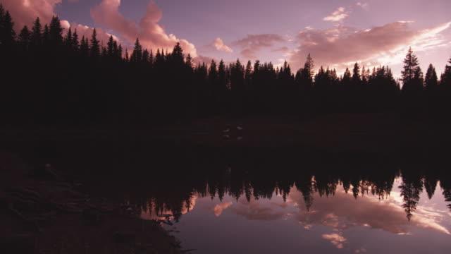 Pan right, silhouetted woods near Utah lake