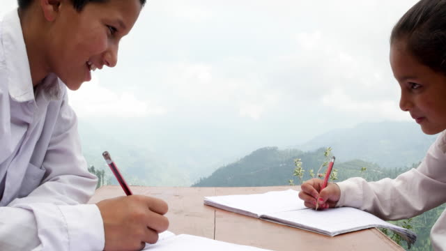 pan right to a boy and girl in school uniform studiying and doing their home work - pencil sharpener stock videos & royalty-free footage