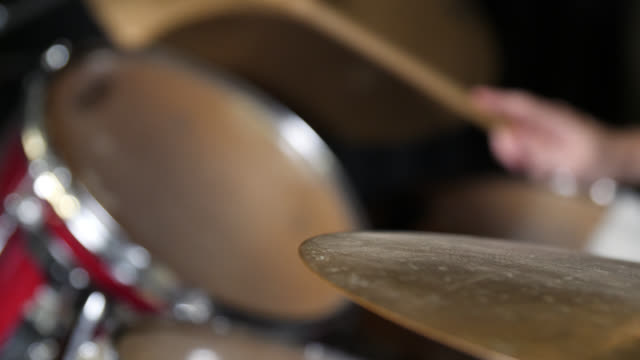 pan right to a crash cymbal on a drum kit with a drummer out of focus in the background - cymbal stock videos and b-roll footage