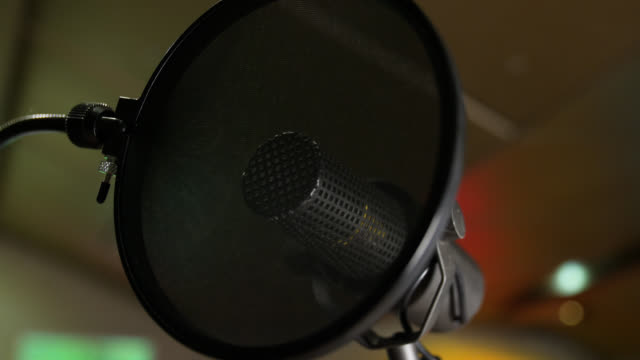Pan right to a microphone behind a pop shield in a recording studio