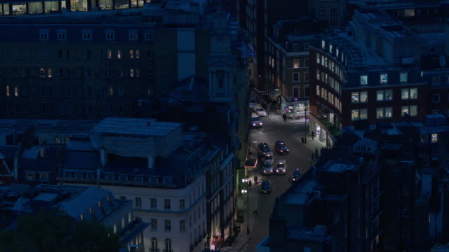 Pan right to an elevated view of a curved London street at twilight, UK.