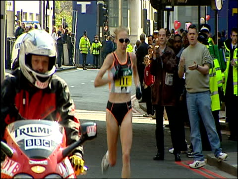 Pan right to follow Paula Radcliffe during 24th mile head nodding running into tunnel cheered on by crowd and followed by motorbike cameras Women's...