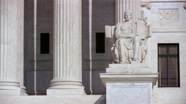 pan right to left across marble figure 'guardian or authority of law' and columns at entrance to us supreme court building / washington, dc - us supreme court building stock videos and b-roll footage