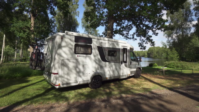 pan right to left: camper parked at the dock waiting for adventure - smaland, sweden - trailer stock videos & royalty-free footage