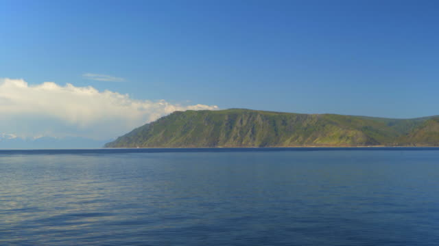 vídeos de stock, filmes e b-roll de pan right to left: green beautiful mountain looking toward the blue lake - lake baikal, russia - indo em direção