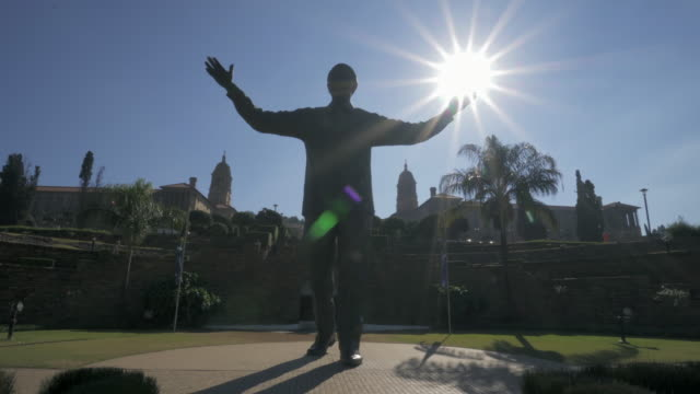 pan right to left: massive statue of the famous nelson mandela in the middle of the nature filled park surrounded by buildings - pretoria, south africa - ネルソン マンデラ点の映像素材/bロール