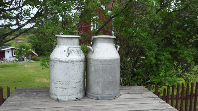 pan right to left: milk metal canister on a table with red home in the background - bullerbyn, sweden - dairy product stock videos & royalty-free footage