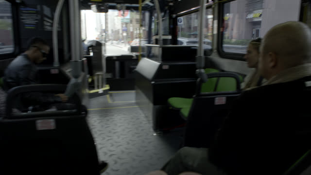 vídeos y material grabado en eventos de stock de pan right to left moving pov of bus on city streets. passengers. - pasajero