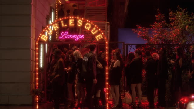 pan right to left of line of people or crowd waiting to get into burlesque lounge. could be bar or nightclub. cars on city street. - entering stock videos & royalty-free footage