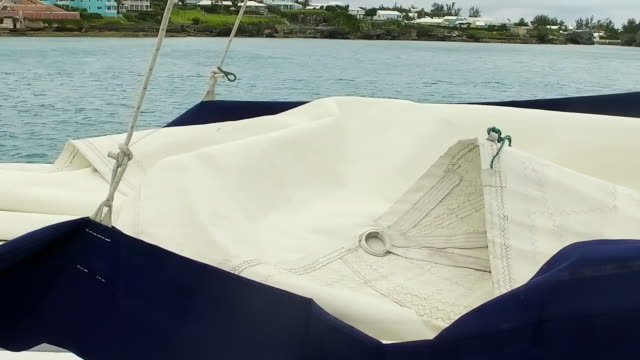 vidéos et rushes de pan right to left: sail of boat folded with water and island in background in hamilton, bermuda - îles de l'atlantique