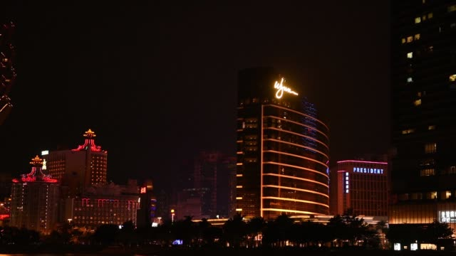 pan right to left, the wynn macau casino resort, operated by wynn resorts ltd., right, the bank of china ltd. building, left, and the casino grand... - ナイトイン点の映像素材/bロール