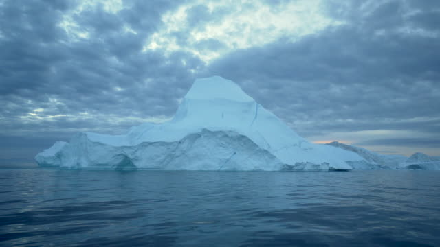 pan right to left: water flowing in the cold area of greenland disko bay - 氷山点の映像素材/bロール