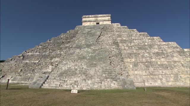 pan right to medium shot of el castillo mayan ruins at chichen itza - pre columbian stock videos & royalty-free footage
