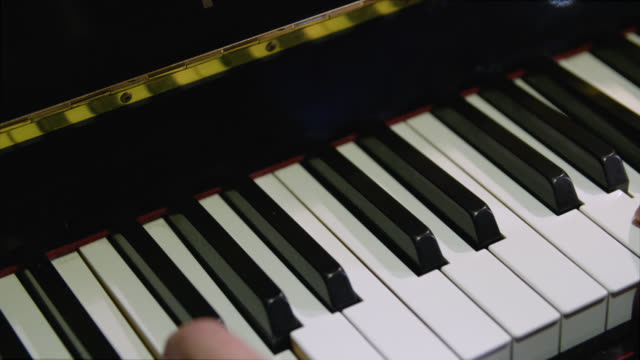 vídeos de stock e filmes b-roll de pan right to notes being played on a piano - pianista