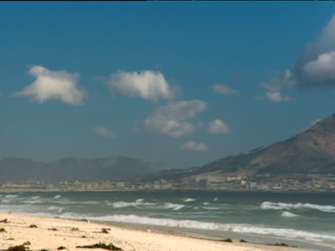 Pan right to Table Mountain with layer of cloud resting on top waves lap onto beach in foreground