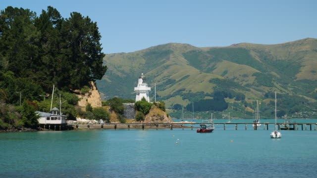 pan right to the peaceful waters of akaroa harbour, new zealand - jetty stock videos & royalty-free footage