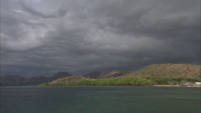 pan right to village on coast of komodo island. - insel komodo stock-videos und b-roll-filmmaterial