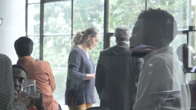 pan right, workers speak after business meeting - softfokus bildbanksvideor och videomaterial från bakom kulisserna