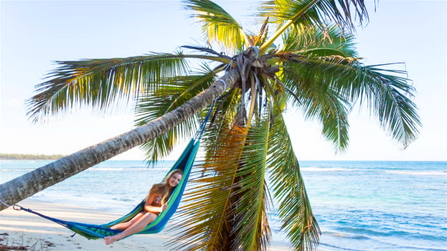 WS pan right, young woman lying in hammock at tropical beach