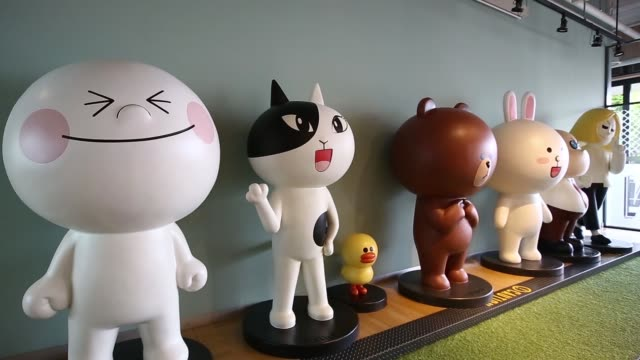 WS pan RL employees sit in the cafeteria MWS pull focus into statues of characters from the messaging application Line stand at a lounge area WS...
