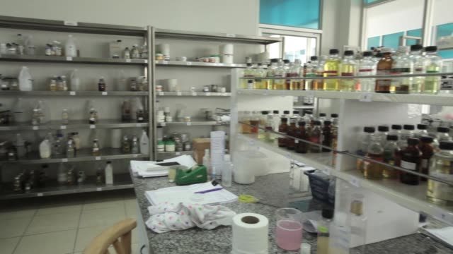 vídeos de stock, filmes e b-roll de pan rl from bottles of cosmetic ingredients sitting on shelves to an employee working in a lab an employee mixes a shower gel solution - produto interno bruto
