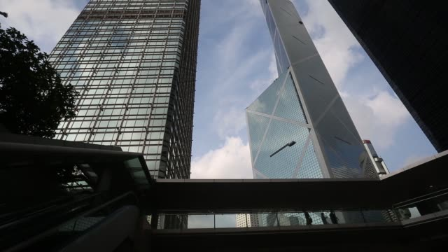 ws pan rl low angle view of pedestrians crossing a footbridge in front of cheung kong center left from bank of china tower right in the central... - bank of china tower hong kong stock videos & royalty-free footage
