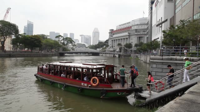 pan rl of housing development board houses at the commonwealth area in singapore on saturday mar 21 tourists enjoy a boat ride at the central... - merlion fictional character stock videos and b-roll footage