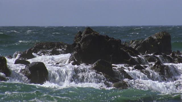 pan rocky shoreline/water crashing onto rocks - horizon over water stock videos & royalty-free footage