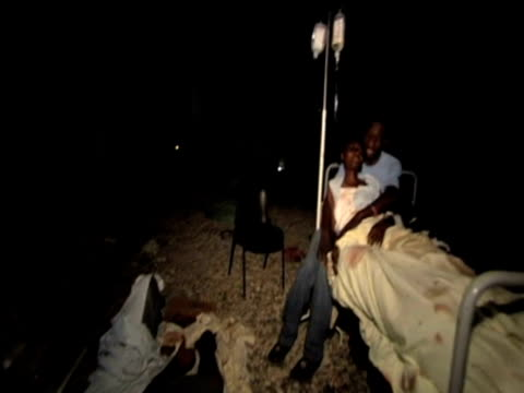 vídeos de stock e filmes b-roll de pan round grounds of hospital as injured woman and her son await medical treatment following devastating earthquake haiti 14 january 2010 - hispaniola
