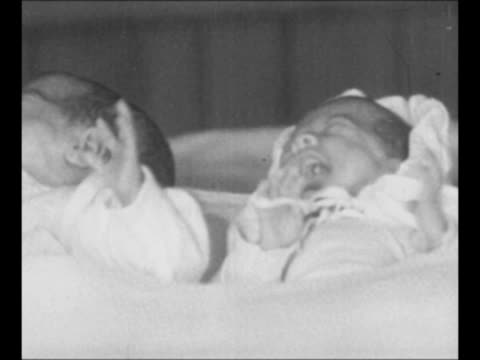 pan cu row of the dionne quintuplets all girls as they lie on a table underneath blankets nurse's hand moves first girl's head second and third girls... - babies in a row stock videos & royalty-free footage