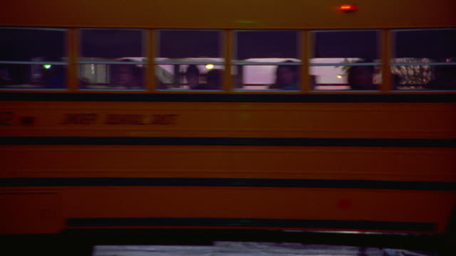 Pan school bus passing in front of camera to reveal main street of small town at sunset / Kansas