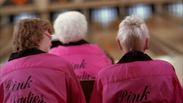 pan senior woman's bowling team in 'pink ladies' jerseys talking and laughing at bowling alley - pink shirt stock videos and b-roll footage