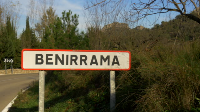 pan shot, Benirrama signpost on curved road, overripe persimmon fruit and village