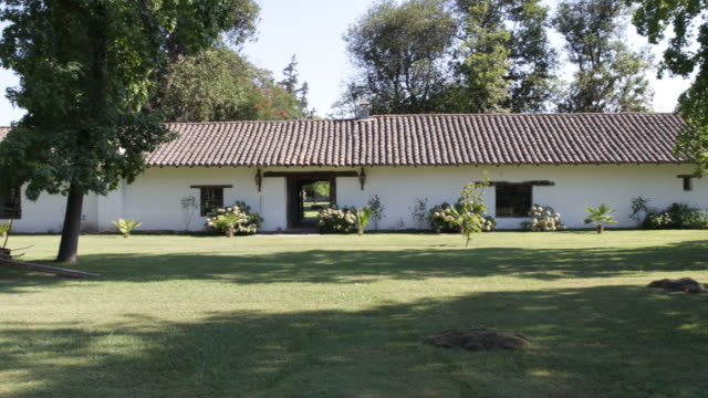 pan shot of a jesuit house seen from the outside in calera de tango chile surrounded by grass some flowers and trees the walls are painted white and... - christian ender stock-videos und b-roll-filmmaterial