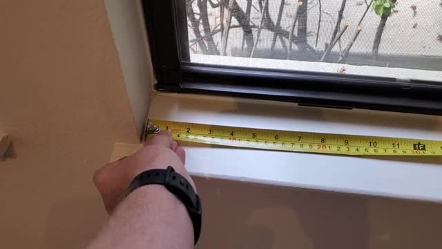 pan shot of a person holding an extended tape measure placed on a window stool, november 11, 2020. - tape measure点の映像素材/bロール