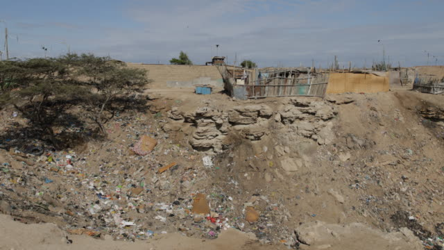 Pan shot of a slum with a lot of trash in Tortuga Peru