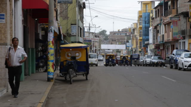 vídeos de stock, filmes e b-roll de pan shot of a street in sullana peru there are rickshaws and cars on the road a man is walking on the sidewalk colorful shop signs are on both sides... - jinriquixá puxado por bicicleta