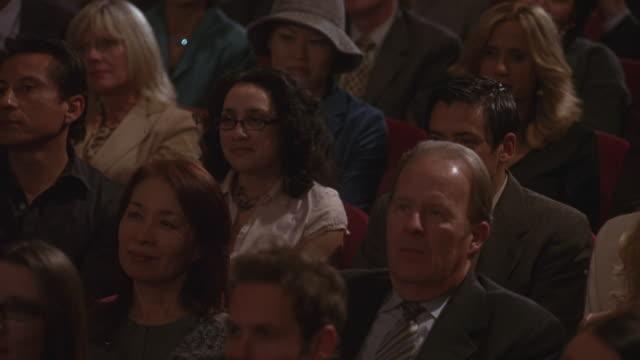 Pan shot of an audience sitting in an auditorium.
