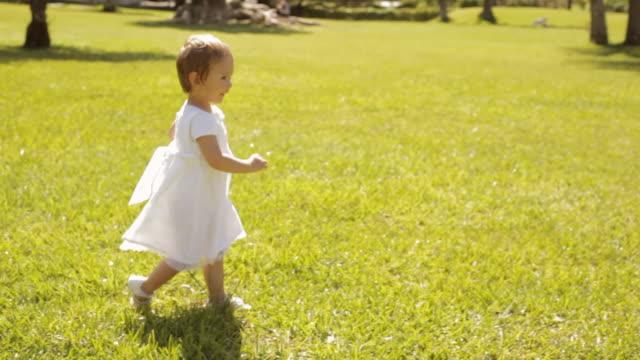 pan shot of baby walking in park