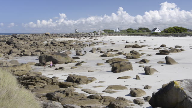 pan shot of beach at low tide with rock formation - low tide stock videos & royalty-free footage