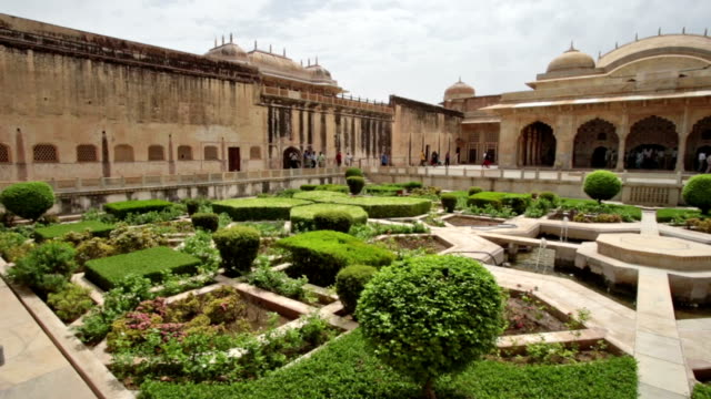 pan shot of beautiful garden in courtyard of ancient stone building. - fortress stock videos and b-roll footage