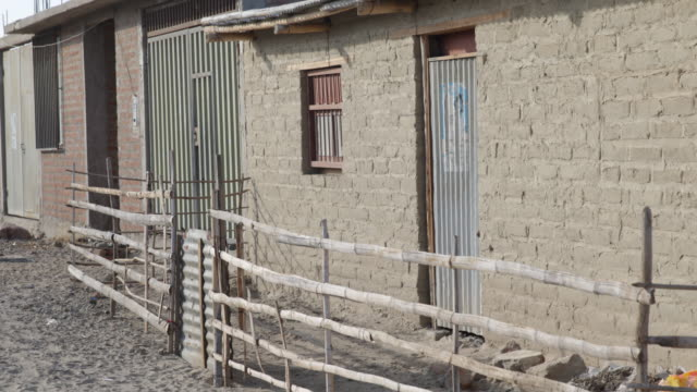pan shot of brick houses with fences in front in a desert slum in piura chile - れんが造りの家点の映像素材/bロール