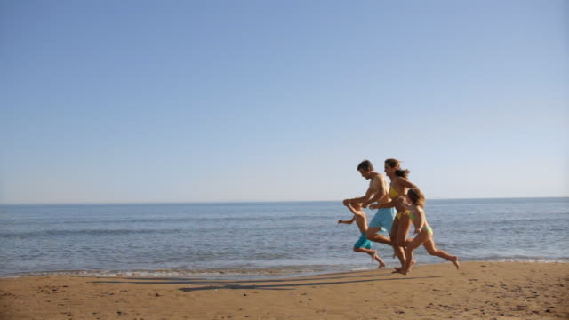 pan shot of family running on beach - four people stock videos & royalty-free footage